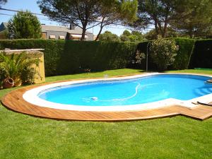 otra vista de la piscina con el borde hecho en madera