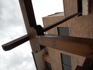 detalle de estructura de pergola en madera de roble con acabado oscuro