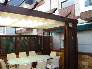pérgola de madera a medida para la terraza, con acabado de techo blanco y celosías decorativas