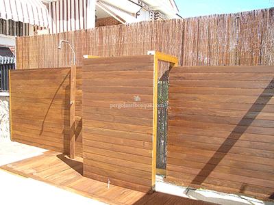 valla de separación de duchas y lavabos en exterior, hecha de madera
