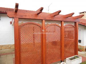 celosías y pérgola en madera combinando en tono con las tejas de la casa