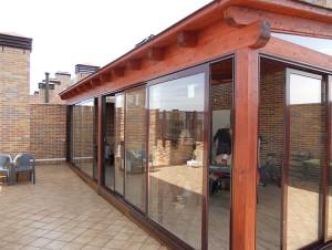 terraza cerrada con puertas de cristal sobre estructura de madera como un porche