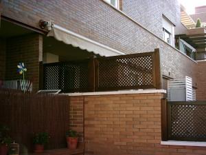 valla de madera con celosia a distinta altura en muro de terraza