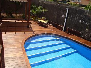 piscina rodeada de suelo de madera hecho a medida