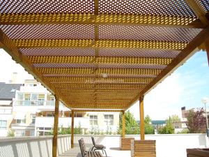 pergola de madera con celosias verticales en el techo y jardineras a juego también en madera