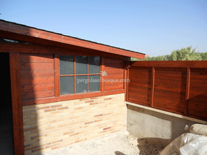 caseta de madera tratada con tonos rojizos y cerrado murete con valla cerrada