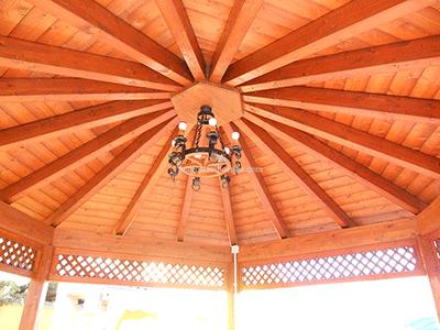 cenador de madera con vigas al punto central y celosías de decoración