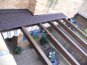 pergola de madera incrustada en muro de vivienda