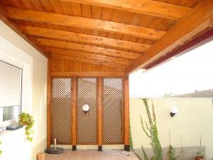 porche cerrado hecho en madera con celosias decorativas