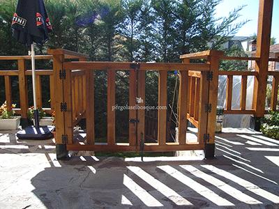 valla de madera con cerramiento a medida que separa el jardín de la casa