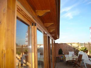 terraza cerrada en madera con puertas y ventanales de cristal para azotea