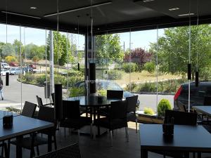 restaurante con cerramiento de cristal y madera con toque elegante
