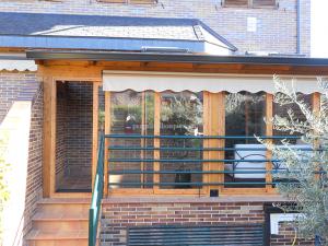 terraza en madera y cerramientos acristalados con toldo
